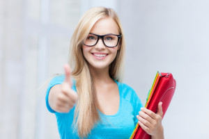 picture of smiling student with folders showing thumbs up
